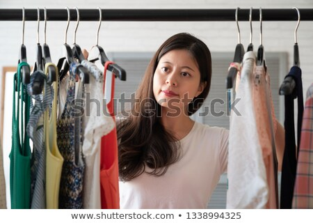 Stok fotoğraf: Woman Picking Clothes Out Of Closet