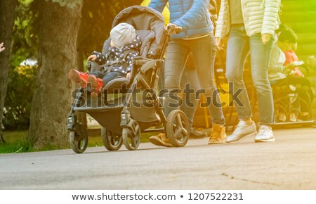 Mother pushing pram with daughter Stock photo © IS2
