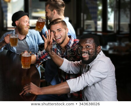 Smiling man with a mug of beer foam. African American people Stock photo © rogistok
