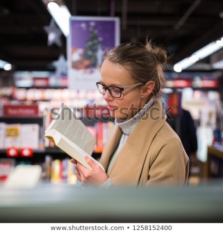 Pretty, young female choosing a good book to buy in a bookstore Stock photo © lightpoet