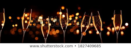 sparkling glasses of champagne on black background bokeh effect stock photo © marysan