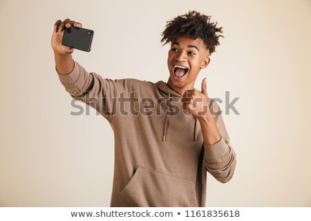 Afro american man dressed in hoodie taking a selfie isolated while showing thumbs up gesture. Stock photo © deandrobot
