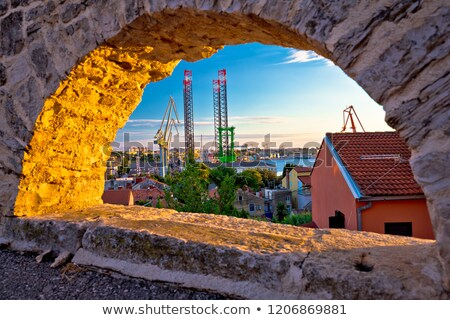 Town of Pula coast and shipyard cranes sunset view through stone Stock photo © xbrchx