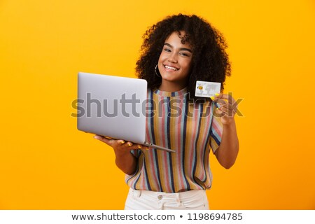 emotional african woman posing isolated over yellow background using laptop computer holding credit stock photo © deandrobot