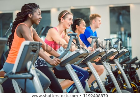 Confident young man smiling during indoor cycling class in a modern fitness club Stock photo © Kzenon