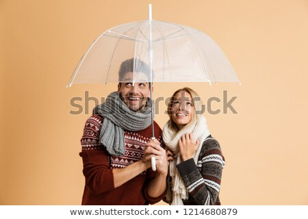 excited young loving couple in scarfs isolated over beige background holding umbrella stock photo © deandrobot