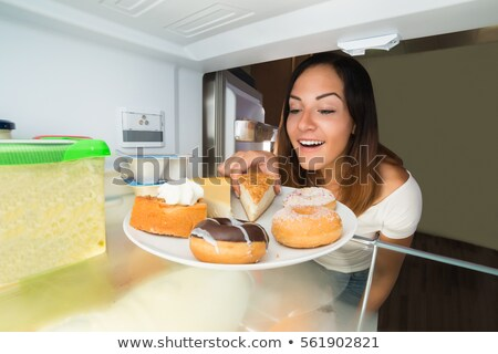 happy woman taking donut from plate stock photo © andreypopov