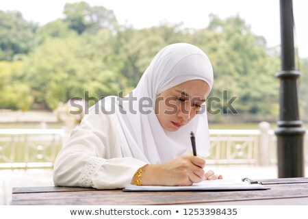 Happy muslim young woman sitting outdoors in park writing notes. Stock photo © deandrobot