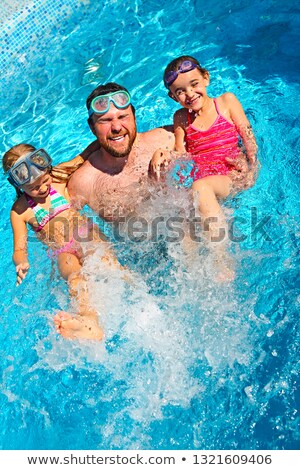 young dad and little daughter splaying in swimming pool enjoying stock photo © dashapetrenko
