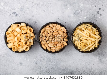 Ready salted potato rings with salt and vinegar sticks and roasted peanuts as classic snack in black Stock photo © DenisMArt