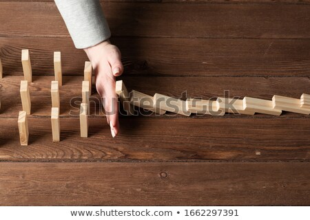 Businesswoman Stopping Dominoes On Desk Stock photo © AndreyPopov