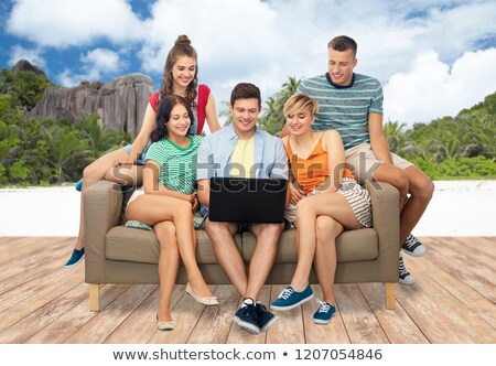 friends sitting on sofa over tropical beach Stock photo © dolgachov
