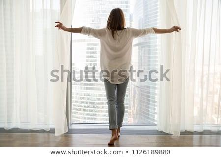 Mulher jovem janela cortinas arranha-céus grande Foto stock © galitskaya