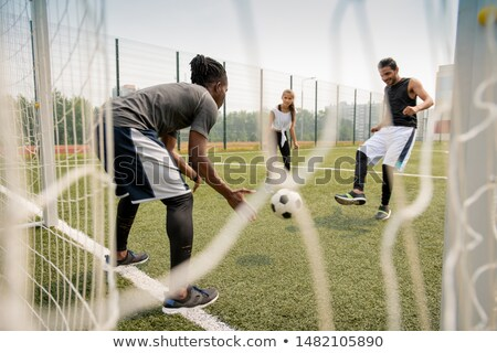 Young African soccer player catching the ball while his rival kicking it Stock photo © pressmaster