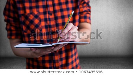 Millennial man mid section with notepad against grey room Stock photo © wavebreak_media