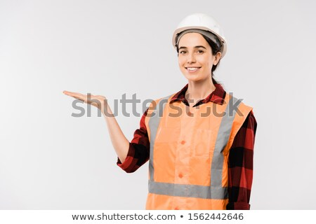 Pretty young smiling female builder in hardhat and workwear presenting something Stock photo © pressmaster