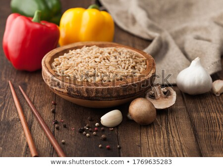 Wooden bowl with boiled long grain risotto rice with mushrooms on wooden table background with stick Stock photo © DenisMArt