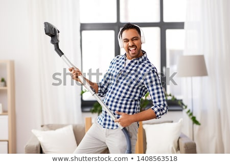 indian man with vacuum cleaner having fun at home Stock photo © dolgachov