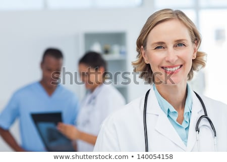 Smiling female doctor in nurse in a lab coat Stock photo © Giulio_Fornasar