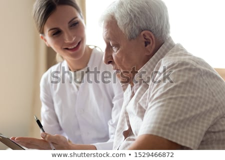 Old female psychiatrist visiting young male patient  Stock photo © Elnur