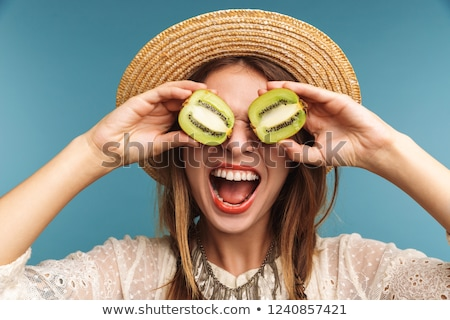 Woman posing isolated over blue wall background with kiwi. Stock photo © deandrobot