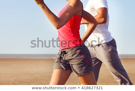 Two athletes runners couple running together on beach. People from behind jogging away barefoot on s Stock photo © Maridav