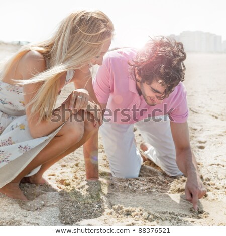 Couple in love drawing a heart in the sand while relaxing at bea Stock photo © HASLOO