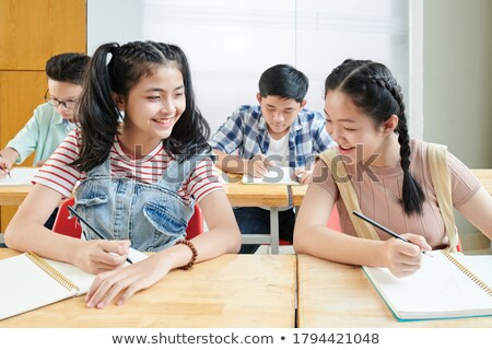 Teenage girl looking at her classmate's answers Stock photo © photography33