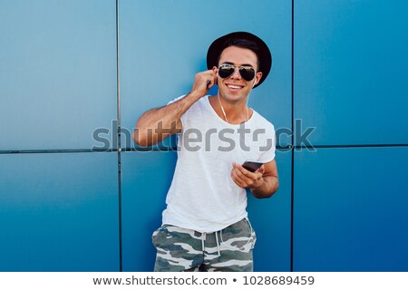 Guy wearing sunglasses and listening to music Stock photo © stockyimages