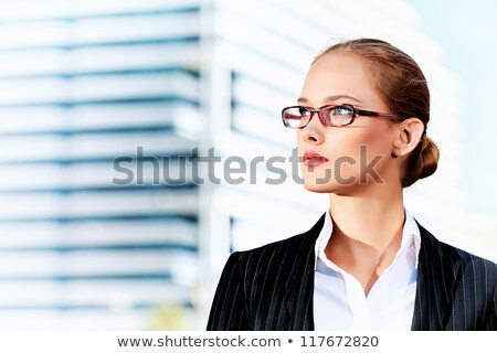 Young woman looking up at the business skyscrapers, conceptual blue tint Stock photo © photocreo