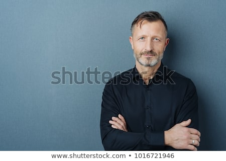 Happy Businessman With Arms Folded Standing On Gray