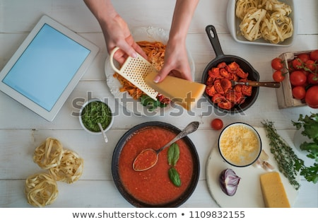 woman cutting vegetables and using a laptop stock photo © imagedb