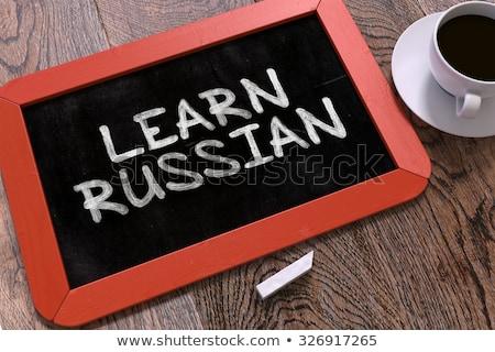 Learn Russian Handwritten by white Chalk on a Blackboard. Stock photo © tashatuvango