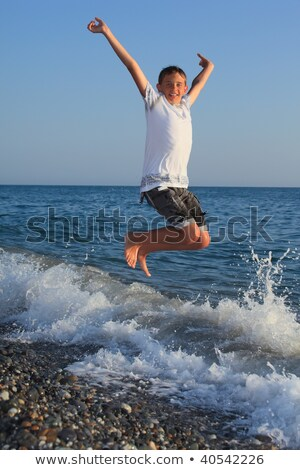 jumping teenager boy on stone seacoast Stock photo © Paha_L