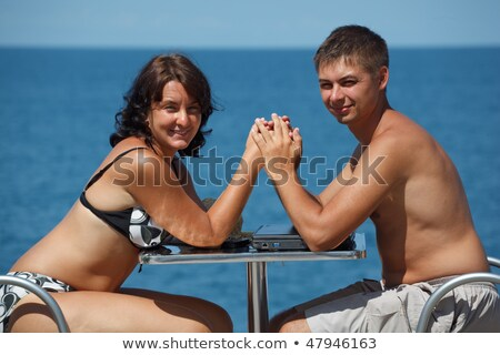 Man and woman sitting at table under open sky on background of sea. Man works for laptop. Girl talki Stock photo © Paha_L