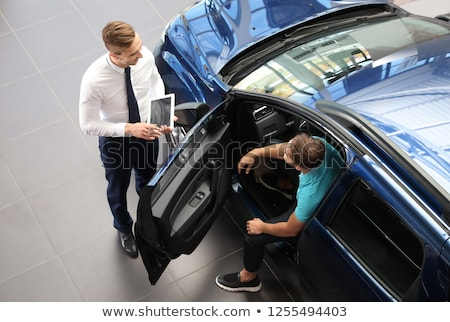 young man or auto dealer in car dealership stock photo © kzenon