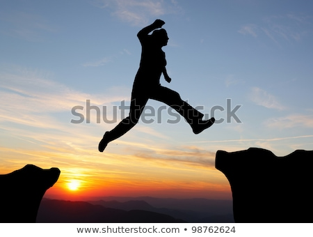 Hiking man jumping over the mountains to success Stock photo © zurijeta