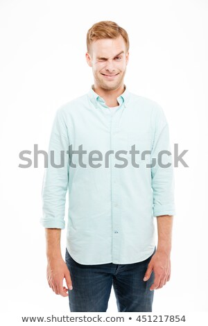 Smiling playful young man making funny face and winking Stock photo © deandrobot