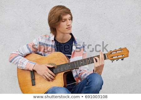 young man holding the guitar while look aside stock photo © deandrobot
