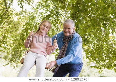 Grandfather pushing granddaughter on swing Stock photo © monkey_business