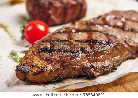 Delicious grilled steak with seasoning on wooden background Stock photo © tommyandone
