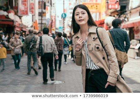 happy relaxed business woman with hands in pockets is walking stock photo © feedough