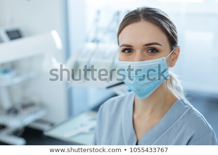 Dentist in face mask working in office Stock photo © IS2