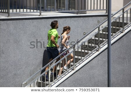 Young couple running upstairs in urban enviroment Stock photo © boggy