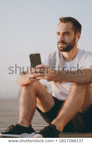 Sportsman outdoors at the beach sitting listening music with earphones drinking water. Stock photo © deandrobot