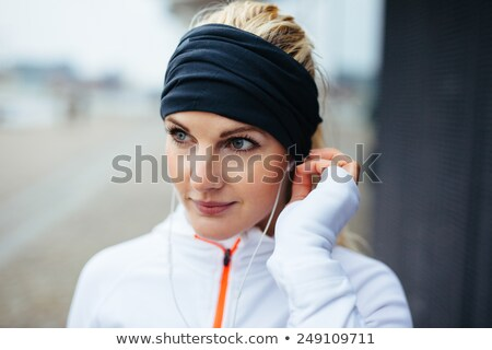 Close up image of sports woman in earphones listening music Stock photo © deandrobot