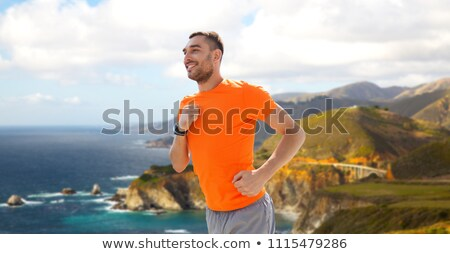happy young man running over big sur coast Stock photo © dolgachov
