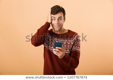 Image of joyous man 20s with stubble wearing knitted sweater usi Stock photo © deandrobot