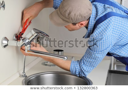 Young plumber repairing tap at kitchen   Stock photo © Elnur