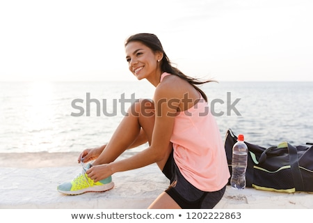 Photo of attractive sporty woman 20s in tracksuit squatting, dur Stock photo © deandrobot